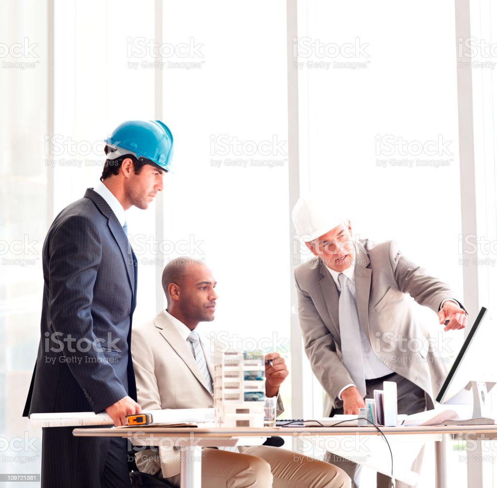 Architects explaining plan to male executive in office royalty-free stock photo