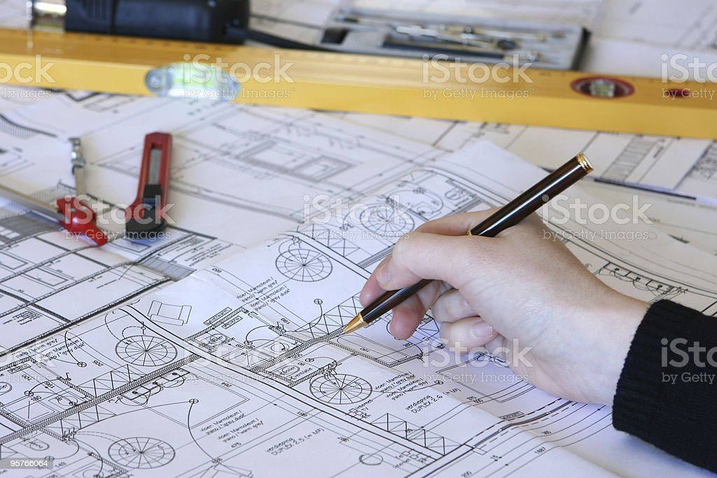 Architect's Hand Working on Building Plans stock photo