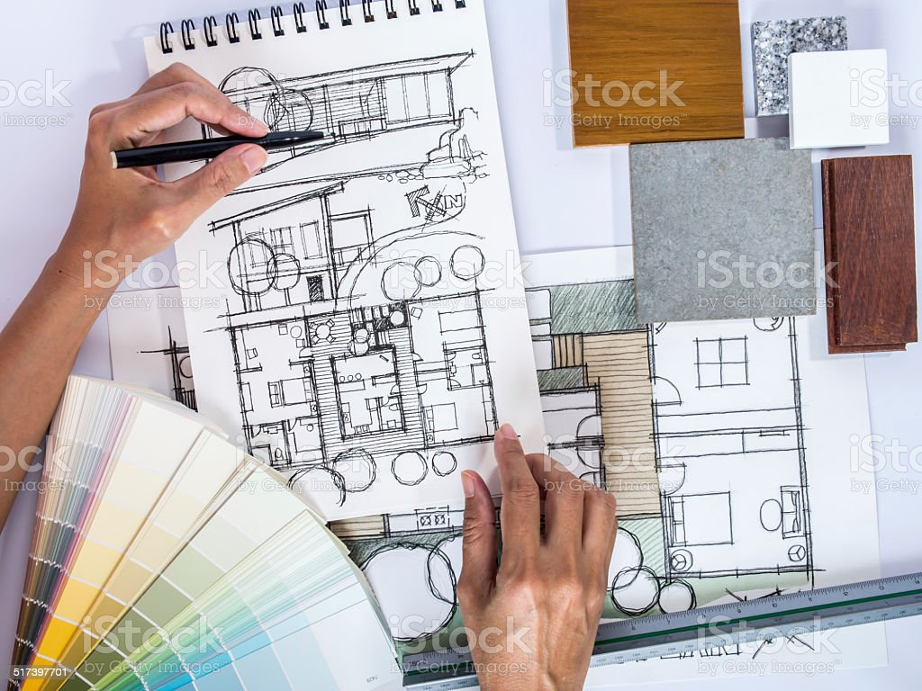 Architect's hands drawing home illustration with material sample stock photo