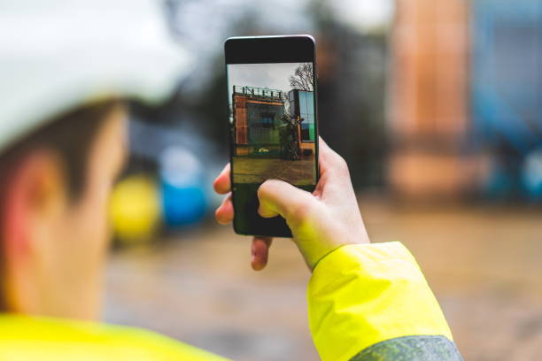 Architects holding a smartphone on construction site - young construction worker is using mobile phone on site - Construction worker with building plans and cellphone - Focus on mobile. warm filter stock photo