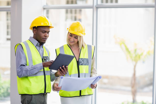 Architects holding blueprint discussing over digital tablet stock photo