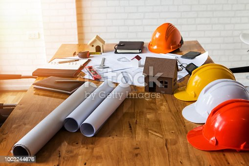 1174841541 istock photo A architects house model with plan and blueprints 1002244676