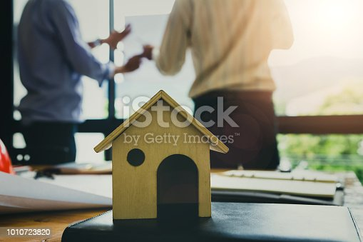 1174841541 istock photo A architects house model with plan and blueprints 1010723820