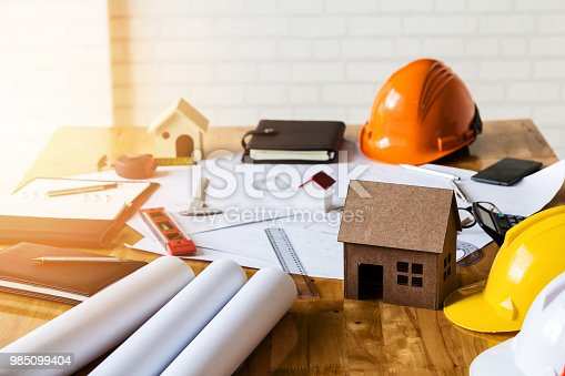 1174841541 istock photo A architects house model with plan and blueprints 985099404