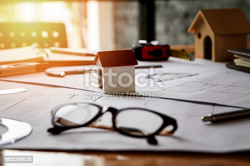 1174841541 istock photo A architects house model with plan and blueprints 985099638
