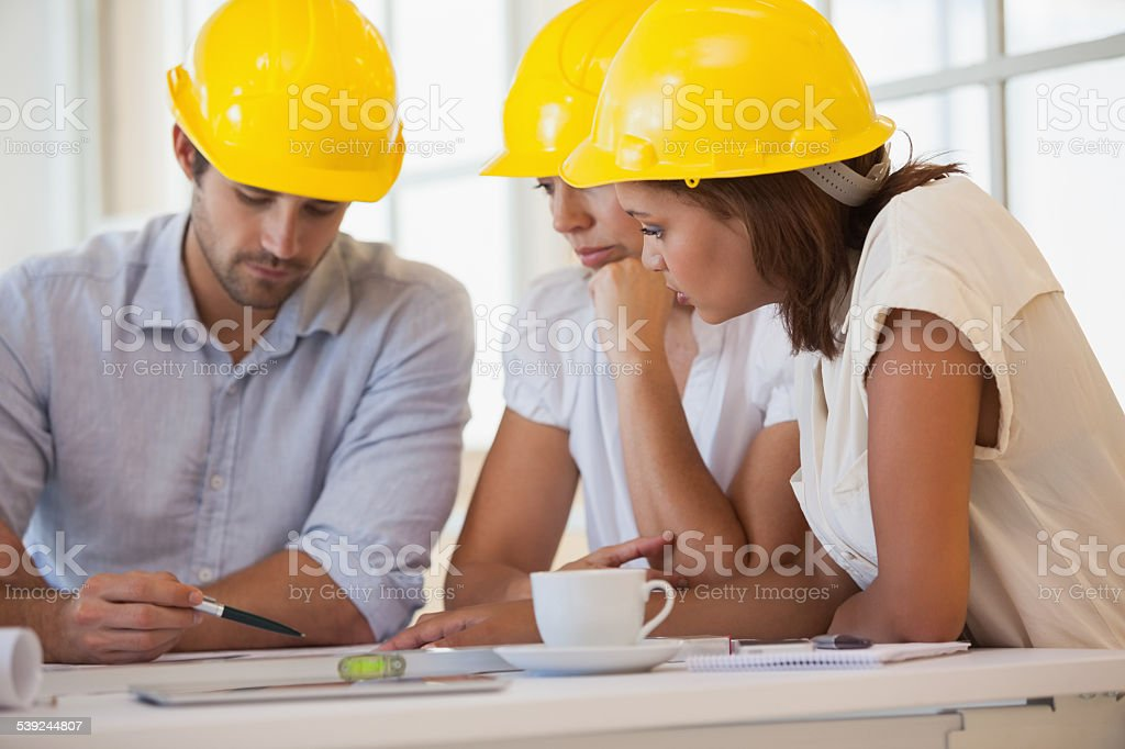 Architects in yellow helmets working on blueprints Concentrated architects in yellow helmets working on blueprints at the office 20-24 Years Stock Photo