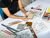 Top view of architects/ interior designer hands working with  shop drawing sketch, material sample on creative table top