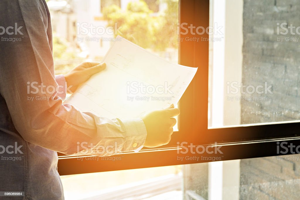 Architects look at paper plan business with sunlight royalty-free stock photo