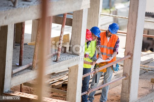 516607254istockphoto Architects looking at blue print outdoor 516597770