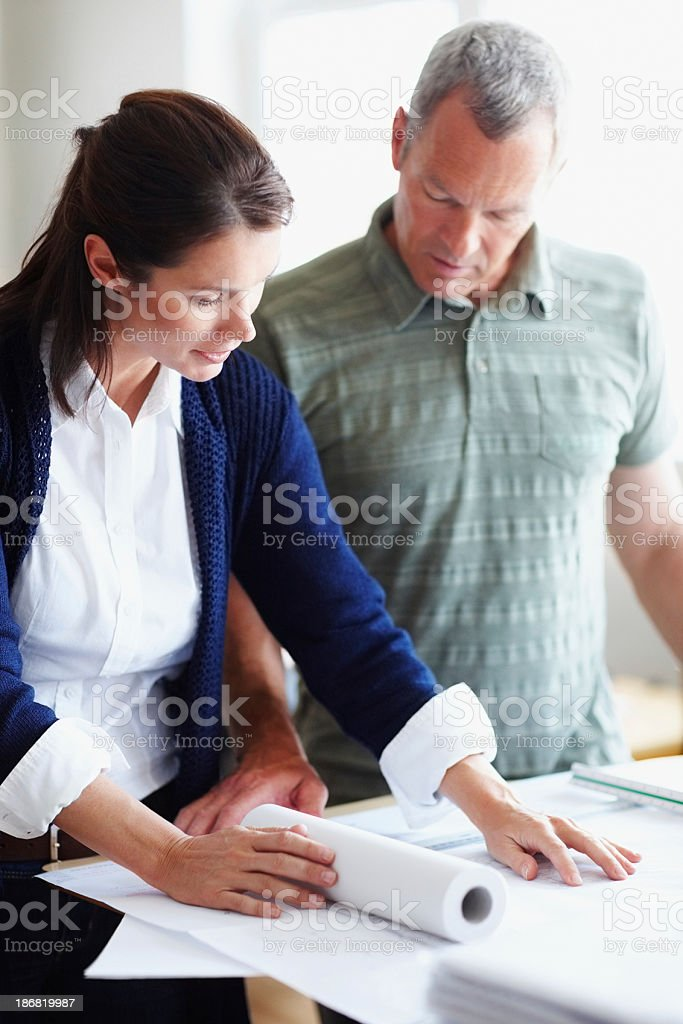 Architects looking at blueprint and discussing a new project royalty-free stock photo