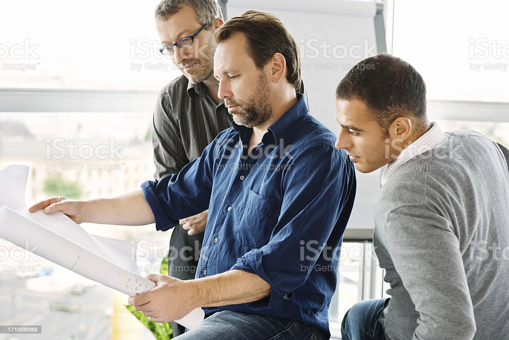 Architects Looking At Blueprint stock photo