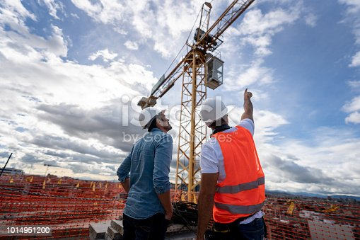 Architects looking at the view from a construction site and pointing at a crane