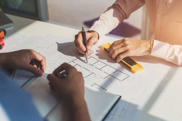 Architects meeting about construction project of house with blueprints in office. Construction and structure concept stock photo
