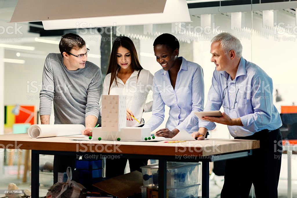Senior Architect with his team reviewing blueprint and architectural...