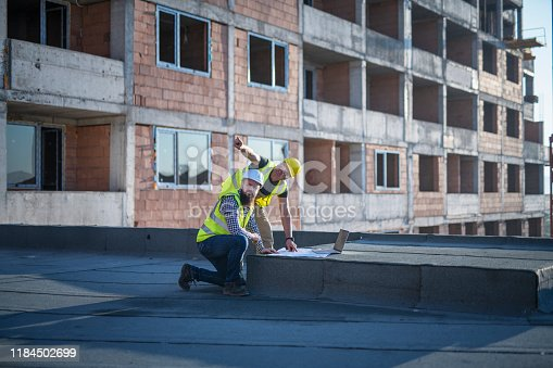 1166176793 istock photo Architects reviewing blueprints on construction site. 1184502699