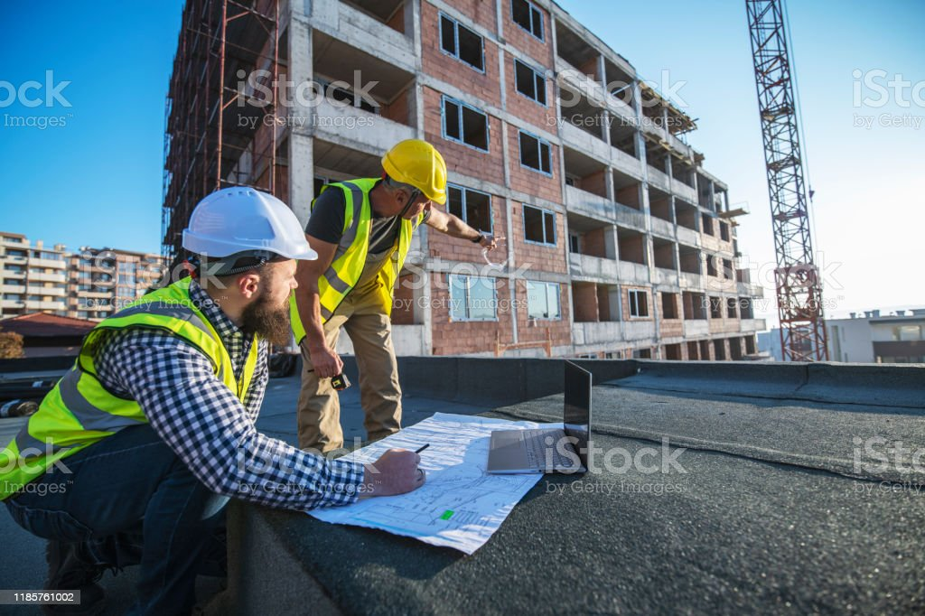 Architects reviewing blueprints on construction site. Architects on construction site reviewing architectural plans, blueprints. 40-44 Years Stock Photo