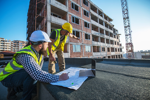 Architects Reviewing Blueprints On Construction Site Stock Photo - Download Image Now