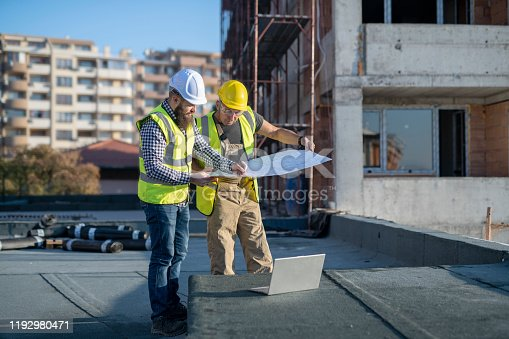 1166176793 istock photo Architects reviewing blueprints on construction site. 1192980471