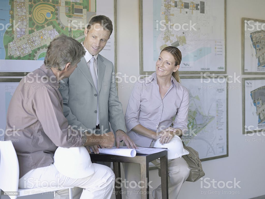 Architects talking in front of urban development plans royalty free stockfoto