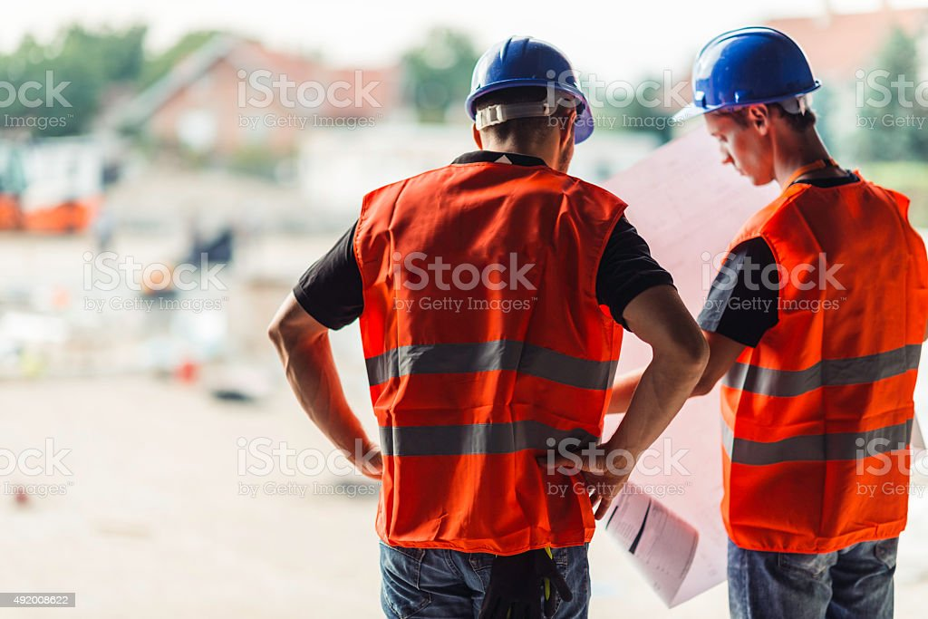 Architects with blueprints on construction site stock photo