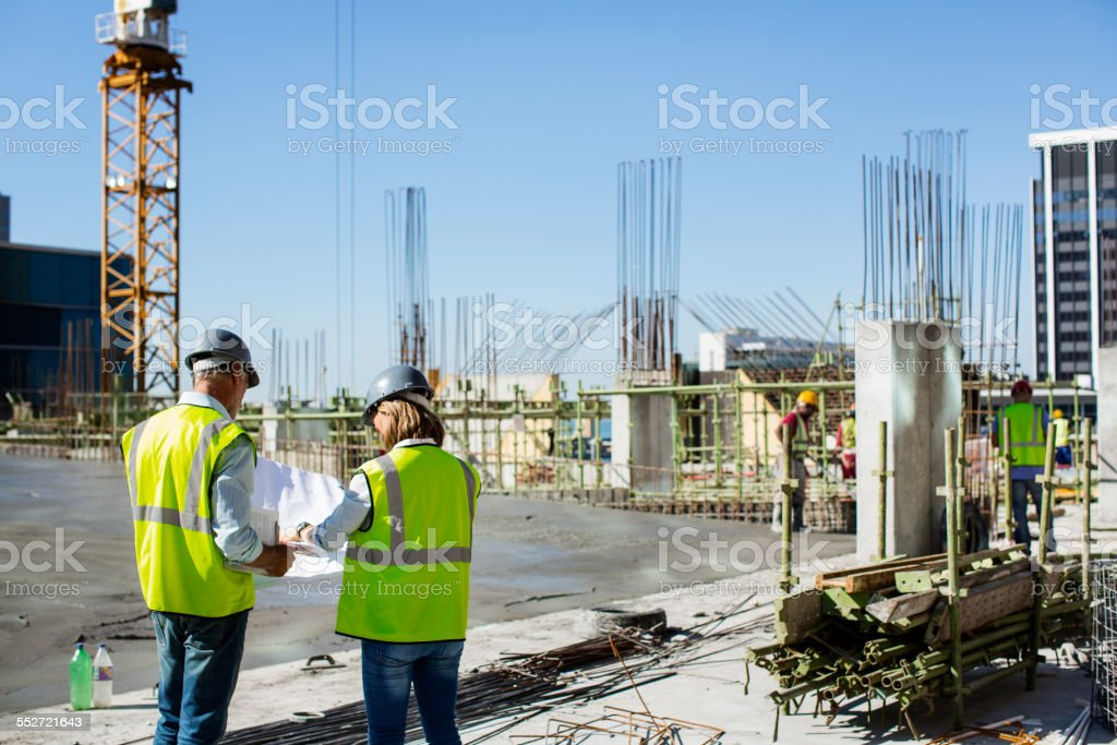 Architects working on blueprint at site stock photo