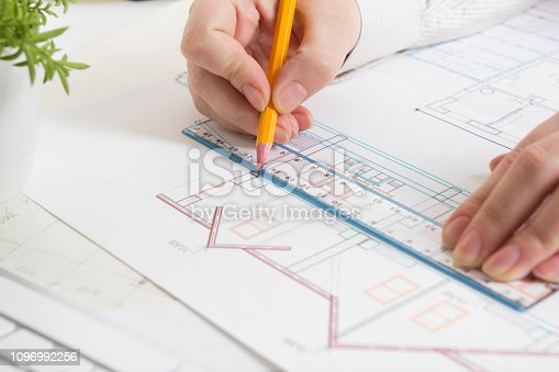 istock Architects working on blueprint, real estate project. Architect workplace - architectural project, blueprints, ruler, calculator, laptop and divider compass. Construction concept. Engineering tools. 1096992256