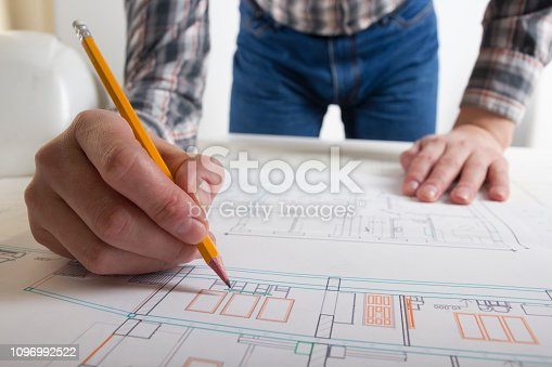 istock Architects working on blueprint, real estate project. Architect workplace - architectural project, blueprints, ruler, calculator, laptop and divider compass. Construction concept. Engineering tools. 1096992522