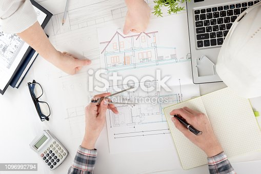 istock Architects working on blueprint, real estate project. Architect workplace - architectural project, blueprints, ruler, calculator, laptop and divider compass. Construction concept. Engineering tools. 1096992794