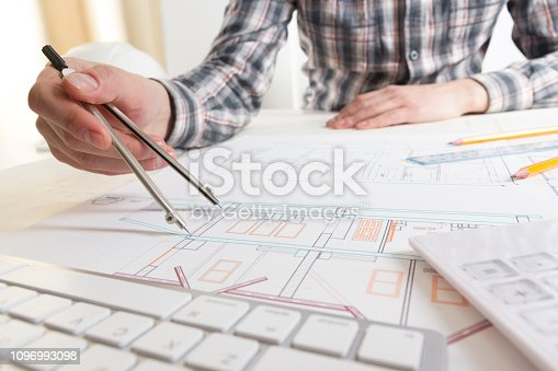 476601452 istock photo Architects working on blueprint, real estate project. Architect workplace - architectural project, blueprints, ruler, calculator, laptop and divider compass. Construction concept. Engineering tools. 1096993098
