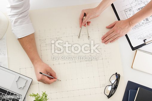 istock Architects working on blueprint, real estate project. Architect workplace - architectural project, blueprints, ruler, calculator, laptop and divider compass. Construction concept. Engineering tools. 1096993264