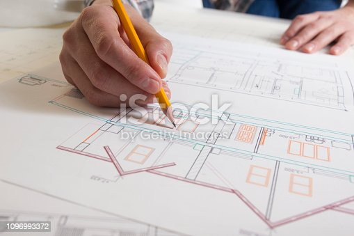 istock Architects working on blueprint, real estate project. Architect workplace - architectural project, blueprints, ruler, calculator, laptop and divider compass. Construction concept. Engineering tools. 1096993372