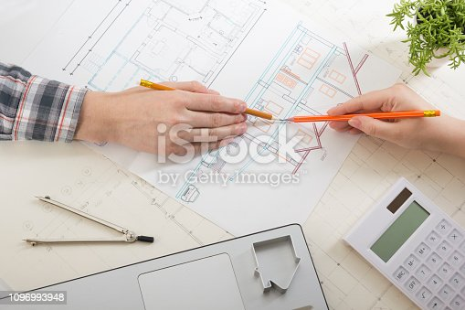 istock Architects working on blueprint, real estate project. Architect workplace - architectural project, blueprints, ruler, calculator, laptop and divider compass. Construction concept. Engineering tools. 1096993948