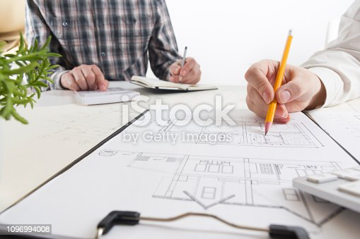 istock Architects working on blueprint, real estate project. Architect workplace - architectural project, blueprints, ruler, calculator, laptop and divider compass. Construction concept. Engineering tools. 1096994008