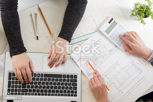 istock Architects working on blueprint, real estate project. Architect workplace - architectural project, blueprints, ruler, calculator, laptop and divider compass. Construction concept. Engineering tools. 1096995174
