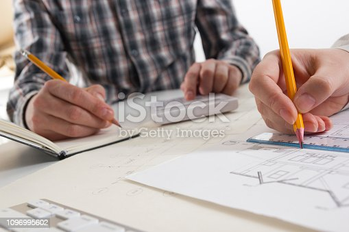 istock Architects working on blueprint, real estate project. Architect workplace - architectural project, blueprints, ruler, calculator, laptop and divider compass. Construction concept. Engineering tools. 1096995602