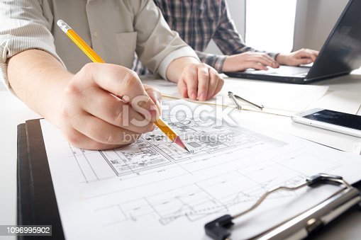 istock Architects working on blueprint, real estate project. Architect workplace - architectural project, blueprints, ruler, calculator, laptop and divider compass. Construction concept. Engineering tools. 1096995902