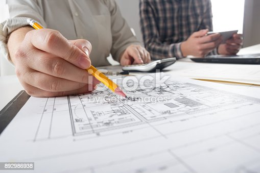 istock Architects working on blueprint, real estate project. Architect workplace - architectural project, blueprints, ruler, calculator, laptop and divider compass. Construction concept. Engineering tools 892986938