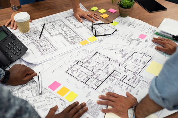 Architects working on blueprints Closeup of multiethnic hands on blueprints at architects office. Team of designer and engineers working together on new residence complex. Top view of blue prints layout of house and buildings on wooden table. blueprint stock pictures, royalty-free photos & images