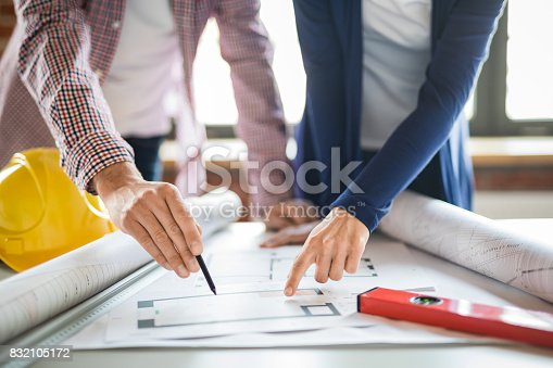 832105172 istock photo Architects working with blueprints in the office. 832105172