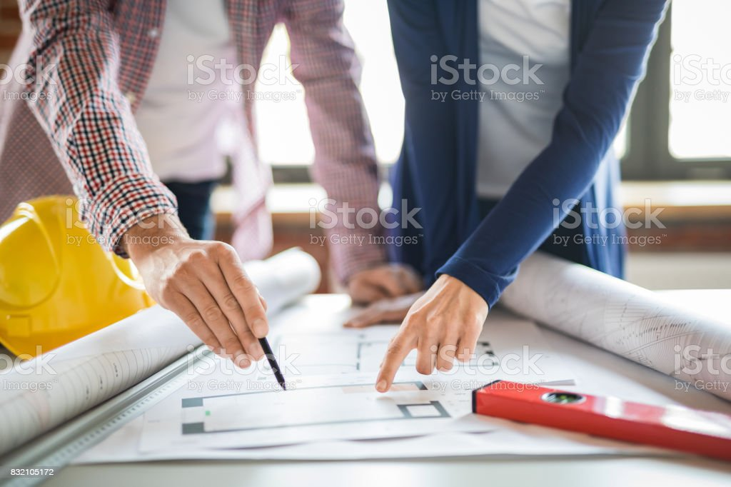 Architects working with blueprints in the office. stock photo
