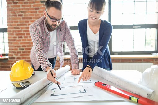 832105172 istock photo Architects working with blueprints in the office. 832108586