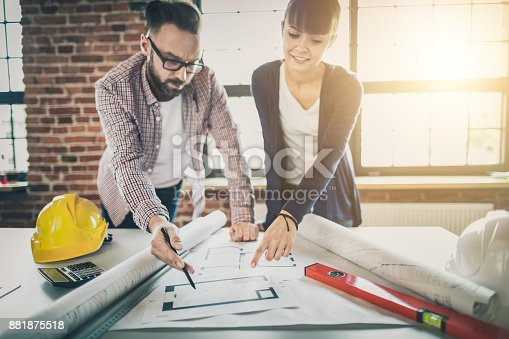 832105172 istock photo Architects working with blueprints in the office. 881875518