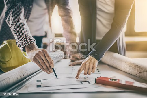 832105172 istock photo Architects working with blueprints in the office. 881876882