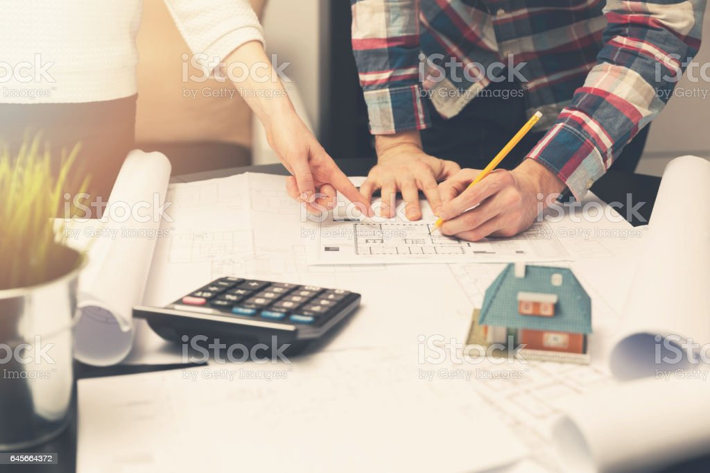 architects working with blueprints on a new house project stock photo