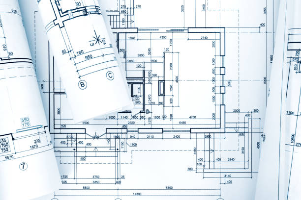 architectural background with blueprint rolls and technical drawings stock photo