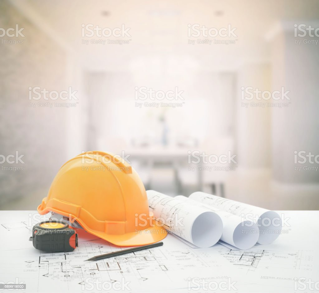architectural blueprint with safety helmet and tools over modern luxury dining room interior. stock photo