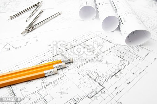 508818208 istock photo Architectural blueprints and blueprint rolls with drawing instruments 533695215