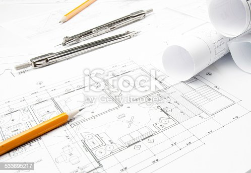508818208 istock photo Architectural blueprints and blueprint rolls with drawing instruments 533695217