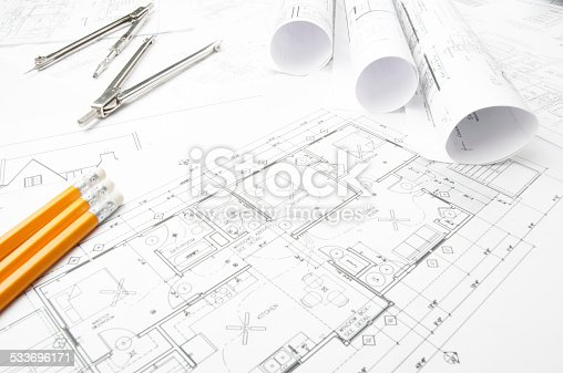 508818208 istock photo Architectural blueprints and blueprint rolls with drawing instruments 533696171