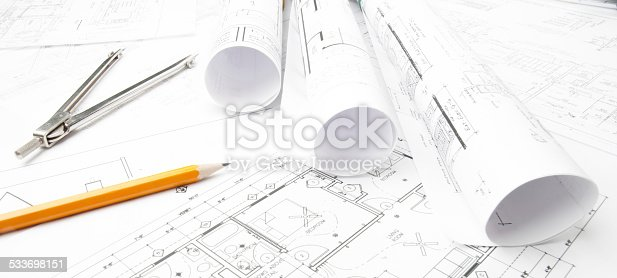 508818208 istock photo Architectural blueprints and blueprint rolls with drawing instruments 533698151